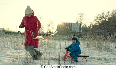 Mother Pulling Sledge with her Smiling Son in Winter -...