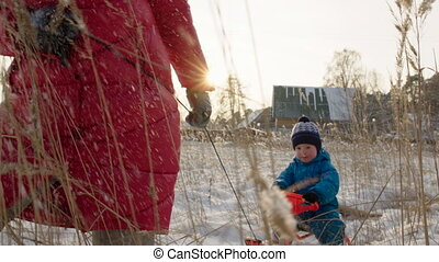 Little Boy Riding the Sledge in Winter Day