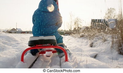 Mother and Son Riding the Sledge in Winter Day - Follow shot...