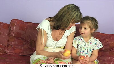 Happy joyful woman with little granddaughter eat delicious apples.