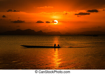 Silhouettes of fisherman at the lake with sunset, Thailand