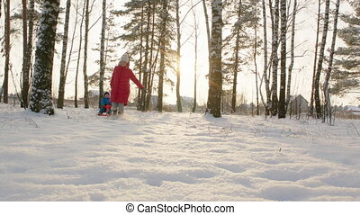 Woman Running and Pulling Toboggan with Little Boy