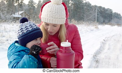 Mother and Son Drinking Hot Beverage from the Thermos Bottle...