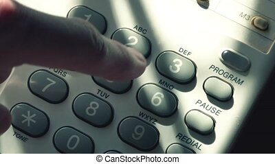 Man dialing random numbers on landline telephone pad, top...
