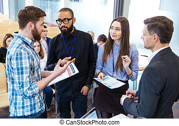 Confident business people standing and discussing financial...