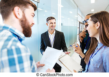 Smiling business people standing and talking with team...