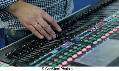 A Sound Engineer Using a Mixing Desk or Mixing Console to...