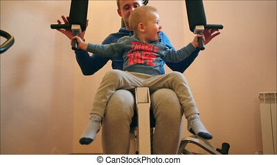 Father and Son Exercising on Weight-Lifting Machine - Little...