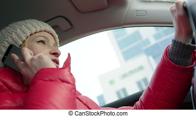 Woman Talking on the Phone while Driving - Low-angle shot of...