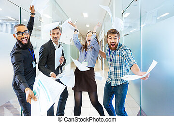 Group of joyful excited business people having fun in office...