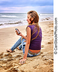 Girl with mobile phone sitting on sand near sea.