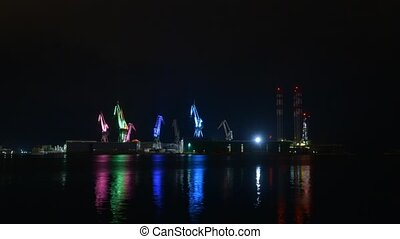 Industrial cargo cranes in the dock glowing in colors