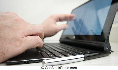 Man working on a notebook using touchscreen, with financial...