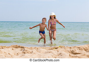 Two kids run out from the sea