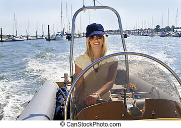 Beautiful Young Blond Woman Driving A Speedboat - A...
