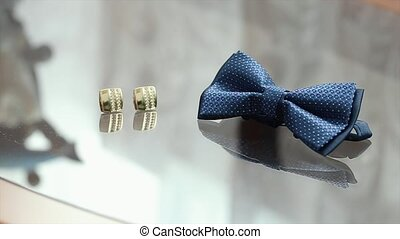 Bowtie and Gold Cufflinks Lying On a Glass Table