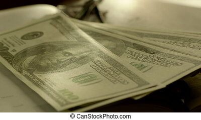 Putting Bundle of Dollar Banknotes on the Book - Someone is...