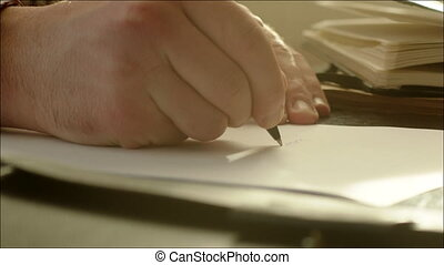 Man Writing on the Paper with Pen - Closeup shot of a white...