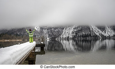Child in winter suit standing on a snowy pier on a beautiful misty lake