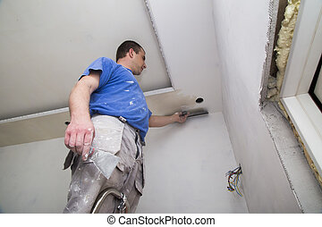 Plasterer with putty knife working