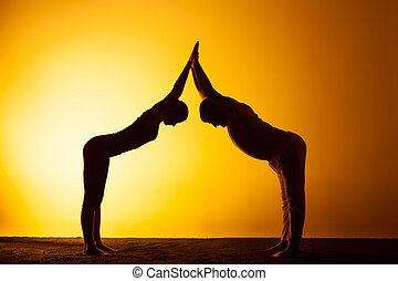 Two people practicing yoga in the sunset light - The two...