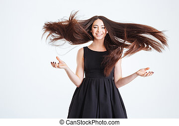 Pretty happy young woman with beautiful long hair in motion...
