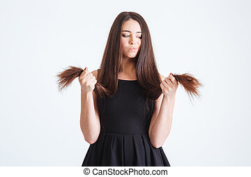 Upset beautiful woman looking on splitting ends of long hair