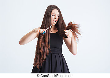 Shocked unhappy woman trimming split ends of hair with scissors