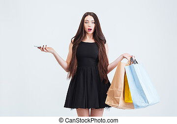 Confused amazed woman holding cell phone and shopping bags