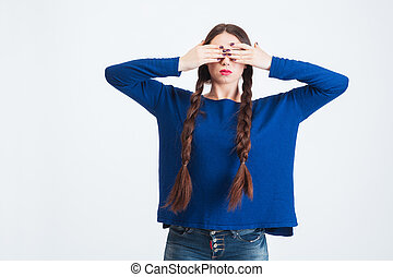 Serious woman with two long braids covered eyes by hands -...