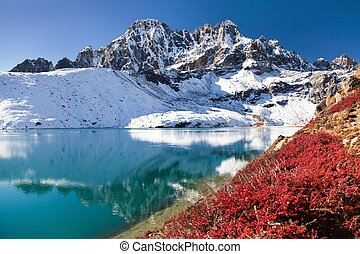 Dudh pokhari Gokyo lake and Phari Lapche peak with red shrub...