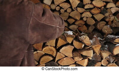 Man take logs from pile of stacked firewood