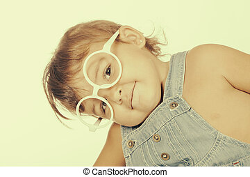Little girl wearing overall and white glasses looking at...
