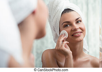 Woman removing make-up - Young natural woman removing...