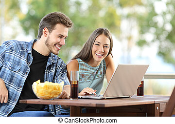 Couple watching media in a laptop outdoors - Couple watching...