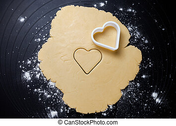 Heart shaped cookie cutter on dough, preparing cookies