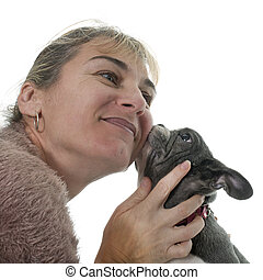 woman kissing bulldog in front of white background