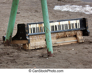The broken piano keyboard, thrown in the yard on sand