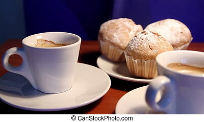 Cups of coffee and muffins on table