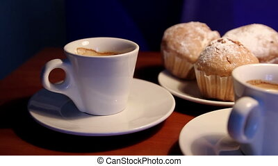 Hands taking a cup of coffee near the muffins