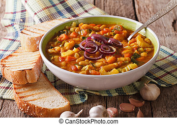 Tuscan ribollita thick soup with bread close up on the...
