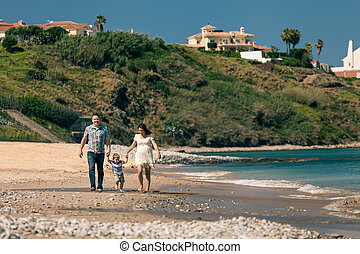 Happy family walking on the coast in Spain - Happy pregnant...
