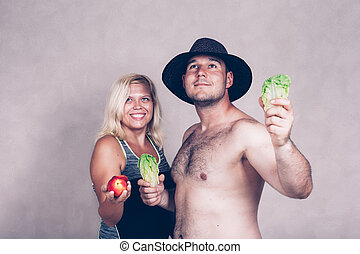 Happy corpulent couple with fruit and vegetable