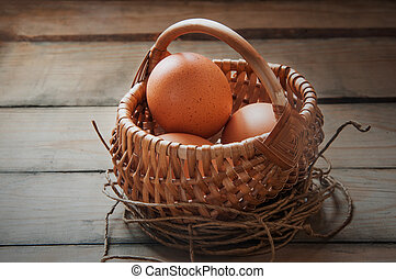 eggs in the basket - Eggs in a basket on a brown wooden...