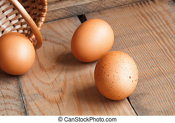 three eggs on the table rolled out of the basket on a wooden...