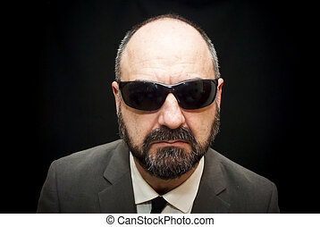 Handsome business man, bald and beard, with sunglasses over...