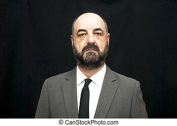 Handsome business man, bald and beard, over black background