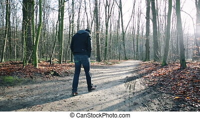 Man walking down path alone - Rear view of single man...