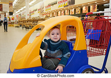 Child in shopping cart - Supermarket store little child...