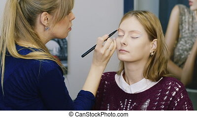Young woman doing her makeup in the salon